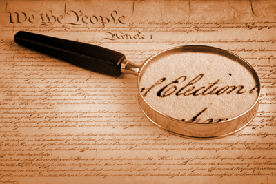 Magnifying glass on American Constitution, emphasising the word Election. We the People in background. Sepia toned. The past connecting with the present.